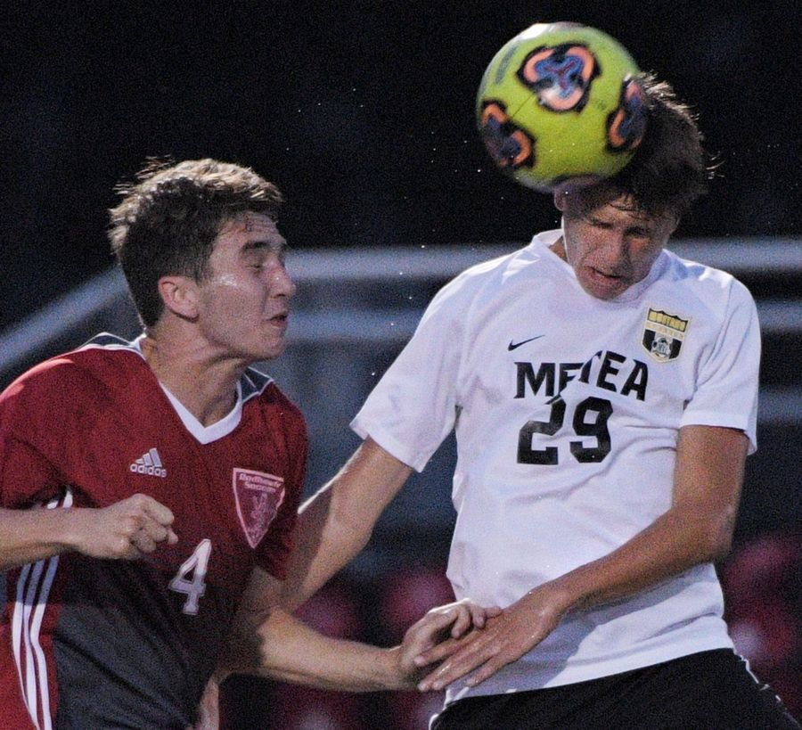 Metea Valley's Alexander Krehl heads the ball against Naperville Central's Mitch Becker in a boys soccer game in Naperville Tuesday.