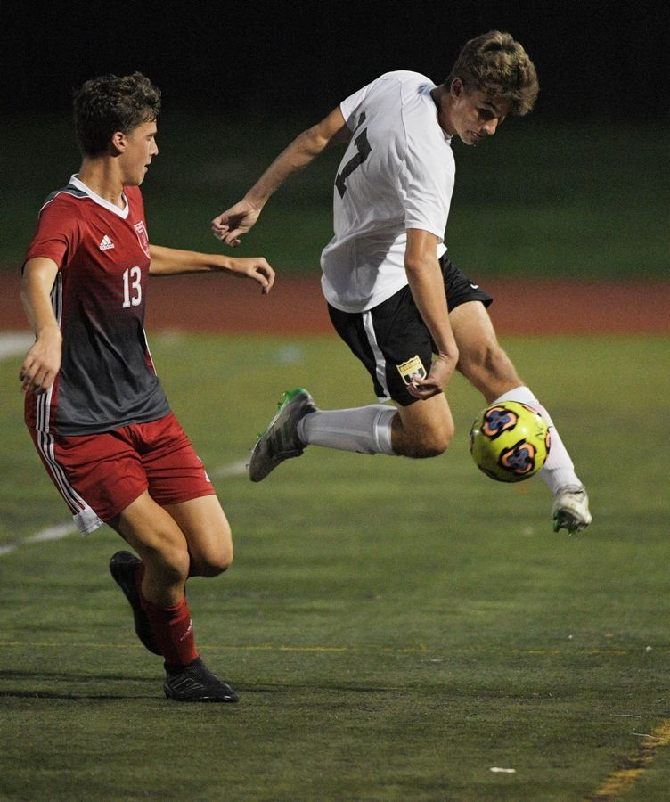 Metea Valley's Mark Thurow keeps the ball inbounds against Naperville Central's Evan Lueckhoff in a boys soccer game in Naperville Tuesday.