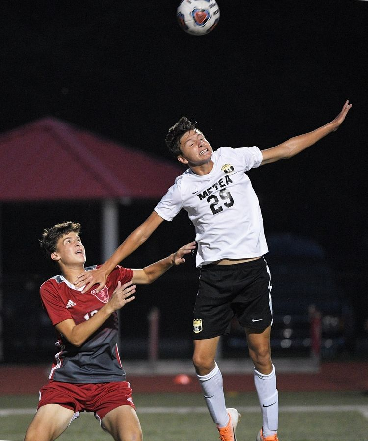 Metea Valley's Alexander Krehl gets above Naperville Central's Evan Lueckhoff in a boys soccer game in Naperville Tuesday.
