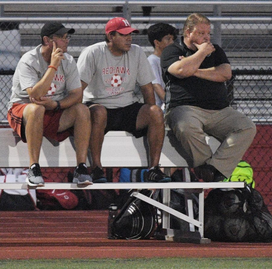 Naperville Central head coach Troy Adams, right, against Metea Valley's in a boys soccer game in Naperville Tuesday.