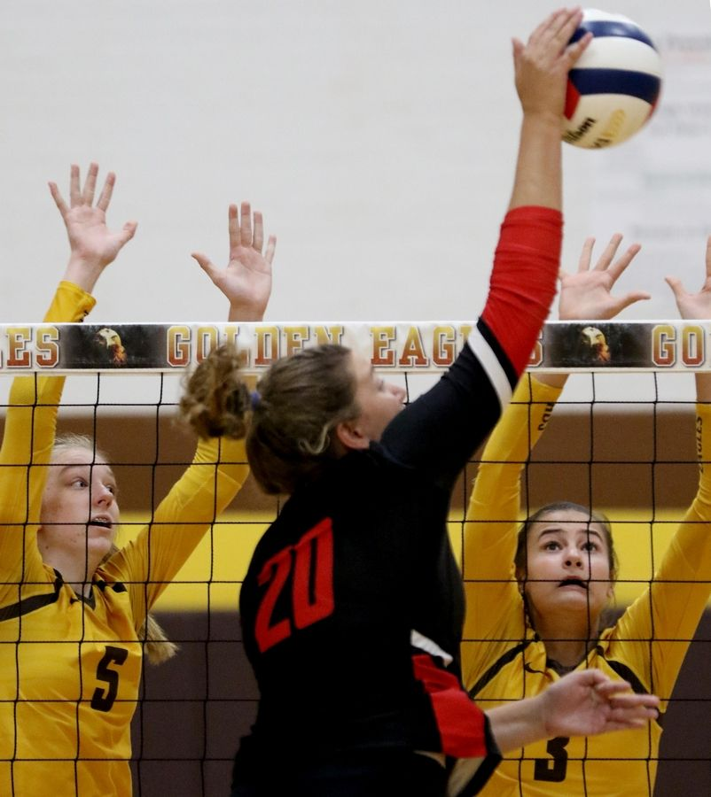 Huntley's Ashley Konecki hits the ball as Jacobs' Rachel Kaczorowski, left, and Jaclyn Poirier defend.