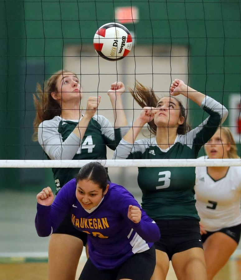 Grayslake Central's Kate Bullman, left, and Taylor Hindman meet Waukegan's Jazmin Cano at the net during their match Tuesday at Grayslake Central High School.