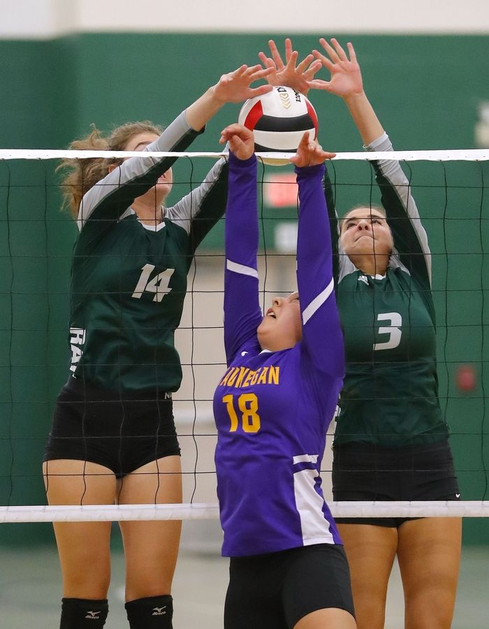 Grayslake Central's Kate Bullman, left, and Taylor Hindman meet Waukegan's Jazmin Cano at the net during their game Tuesday at Grayslake Central High School.