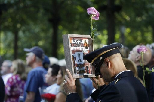 A man holds a photo of a victim during a ceremony marking the 18th anniversary of the attacks of Sept. 11, 2001, at the National September 11 Memorial, Wednesday, Sept. 11, 2019, in New York.