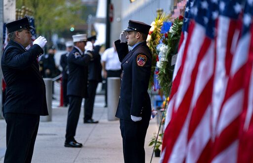 New York City firefighters salute in front of a memorial on the side of a firehouse adjacent to One World Trade Center and the 9/11 Memorial site during ceremonies on the 18th anniversary of 9/11 terrorist attacks in New York on Wednesday, Sept. 11, 2019.