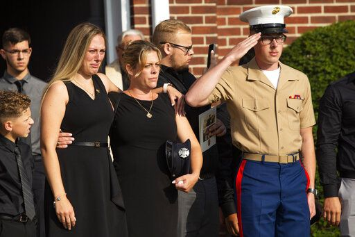 Kiersten Haub, from left, Erika Starke, and Michael Haub, family members of New York firefighter Michael Haub, attend a second funeral service for him in Franklin Square, N.Y., Tuesday, Sept. 10, 2019. The firefighter from New York's Long Island who died in the World Trade Center attacks is being remembered for a second time on the eve of the 18th anniversary of 9/11. Friends and family gathered at the memorial service for Haub on Tuesday in Franklin Square. Last week, the New York City medical examiner identified more of his remains recovered at ground zero.