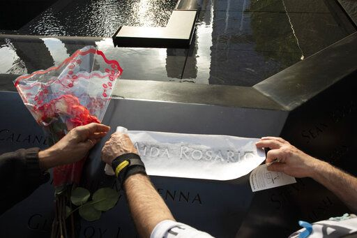 Louis Gonzalez makes a rubbing of his sister's name at the National September 11 Memorial, Wednesday, Sept. 11, 2019 in New York. Aida Rosario was killed during the attacks of Sept. 11, 2001.