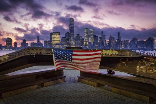 A U.S. flag hanging from a steel girder, damaged in the Sept. 11, 2001 attacks on the World Trade Center, blows in the breeze at a memorial in Jersey City, N.J., Sept. 11, 2019 as the sun rises behind One World Trade Center building and the re-developed area where the Twin Towers of World Trade Center once stood in New York City on the 18th anniversary of the attacks.