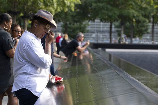 A woman wipes away tears as she stands next to the north pool prior to a ceremony marking the 18th anniversary of the attacks of Sept. 11, 2001 at the National September 11 Memorial, Wednesday, Sept. 11, 2019 in New York.