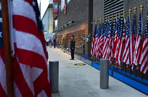 New York City firefighters stand at attention in front of a memorial on the side of a firehouse adjacent to One World Trade Center and the 9/11 Memorial site during ceremonies commemorating the 18th anniversary of the 9/11 terrorist attacks in New York on Wednesday, Sept. 11, 2019.