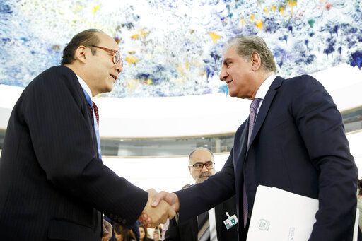 Pakistan's Foreign Minister Shah Mehmood Qureshi, right, shakes hands with China's Ambassador Chen Xu, left, after delivering his statement during the 42nd session of the Human Rights Council at the European headquarters of the United Nations in Geneva, Switzerland, Tuesday, Sept. 10, 2019. (Salvatore Di Nolfi/Keystone via AP)