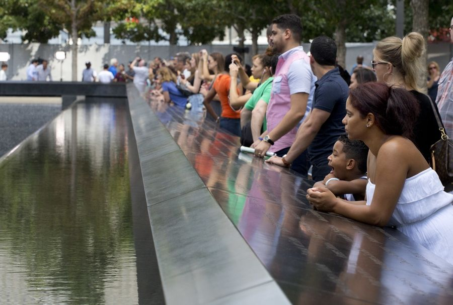 Visitors look at the waterfalls at the World Trade Center Memorial in New York City.