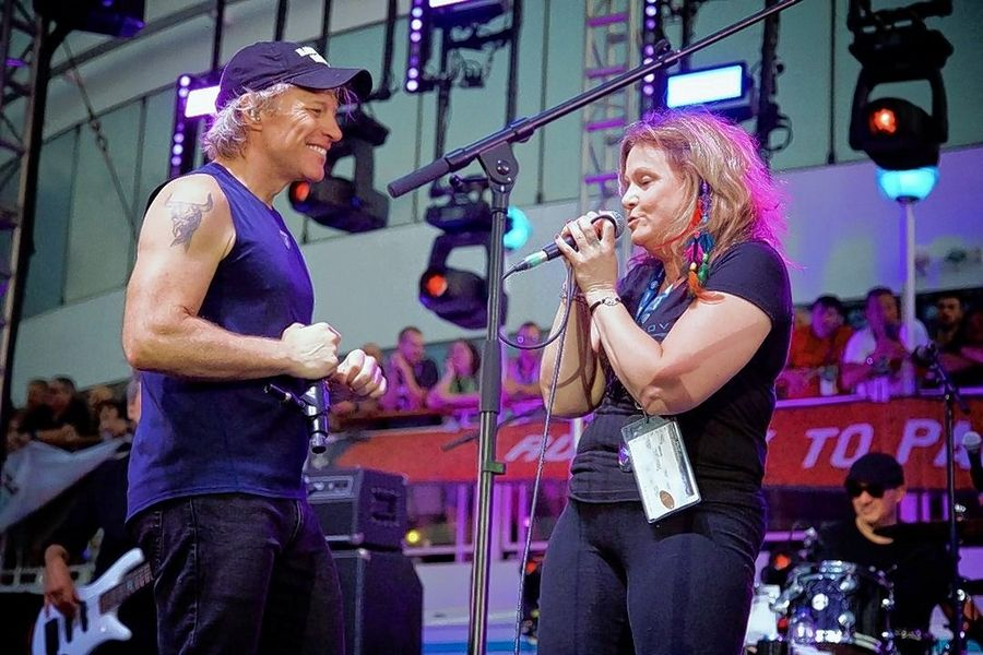 "Michelle Korpalski of Hanover Park shares the stage with Jon Bon Jovi to sing ""Livin' On a Prayer"" at the end of a concert on the Runaway to Paradise cruise in Spain last month."