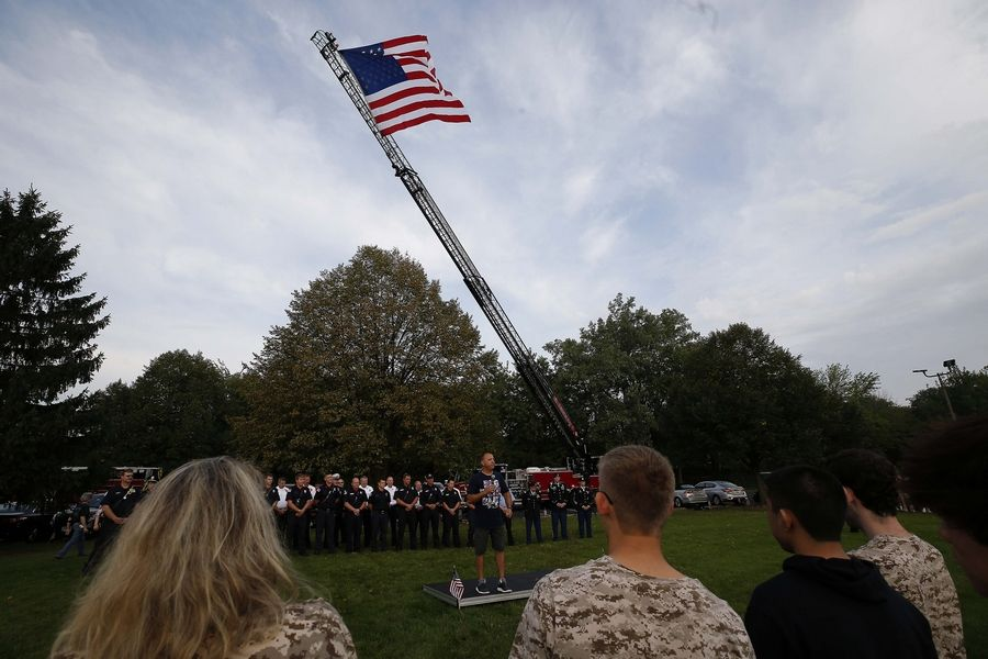 A huge flag is flown from a ladder truck Wednesday as retired Marine Dino Moran, a physical education teacher at Stevenson High School, speaks to students and local first responders gathered in front of the Lincolnshire school for a Sept. 11 remembrance ceremony.