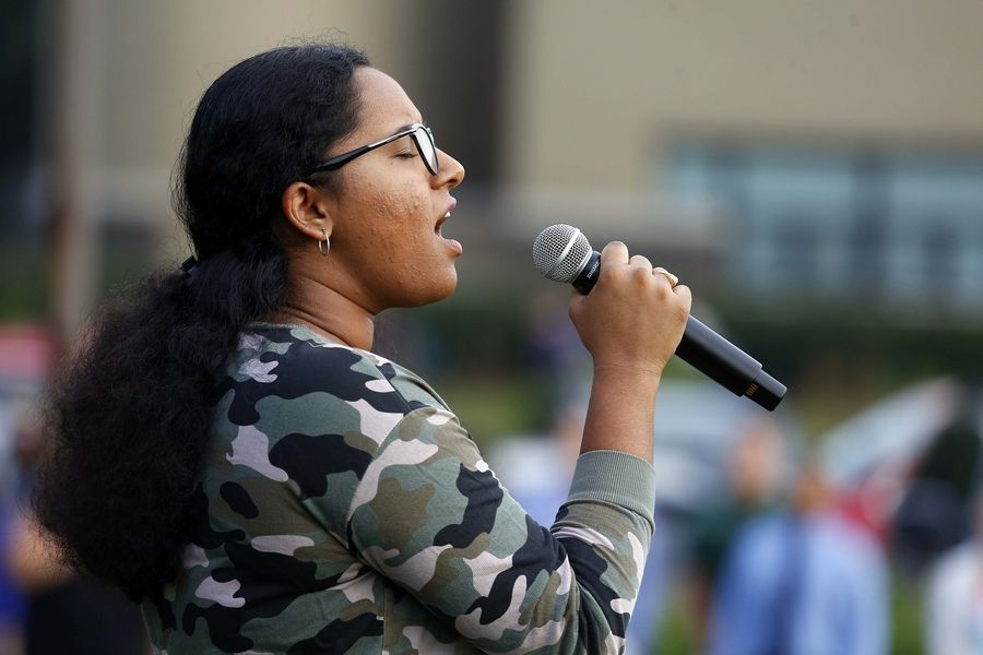 Stevenson High School student Samhita Madduru, 17, sings the national anthem Wednesday during a Sept. 11 remembrance ceremony at the Lincolnshire school.
