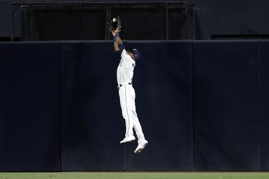 San Diego Padres center fielder Manuel Margot makes the catch above the wall for the out on Chicago Cubs' Nicholas Castellanos during the fourth inning of a baseball game Wednesday, Sept. 11, 2019, in San Diego.