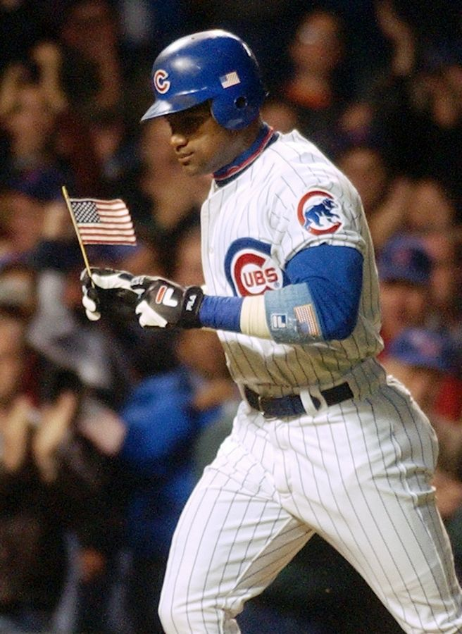 Chicago Cubs' Sammy Sosa carries the American flag Thursday, Sept. 27, 2001 as he rounds the bases after hitting a solo home run against the Houston Astros in the first inning at Wrigley Field in Chicago. It was the Cubs' first home game since the terrorist attacks Sept. 11.