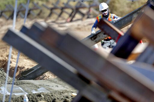 A government contractor, surrounded by existing Normandy barriers that separate Mexico and the United States, pours a concrete footer in preparation for a section of Pentagon-funded border wall along the Colorado River, Tuesday, Sept. 10, 2019 in Yuma, Ariz. A 30-foot high wall will replace the current five-mile section of border comprised of Normandy barriers and post-n-beam fencing. Construction began as federal officials revealed a list of Defense Department projects to be cut to pay for President Donald Trump's wall.