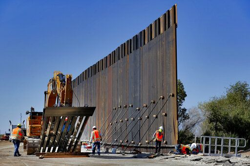 Government contractors erect a section of Pentagon-funded border wall along the Colorado River, Tuesday, Sept. 10, 2019 in Yuma, Ariz. The 30-foot high wall replaces a five-mile section of Normandy barrier and post-n-beam fencing along the the International border that separates Mexico and the United States. Construction began as federal officials revealed a list of Defense Department projects to be cut to pay for President Donald Trump's wall.