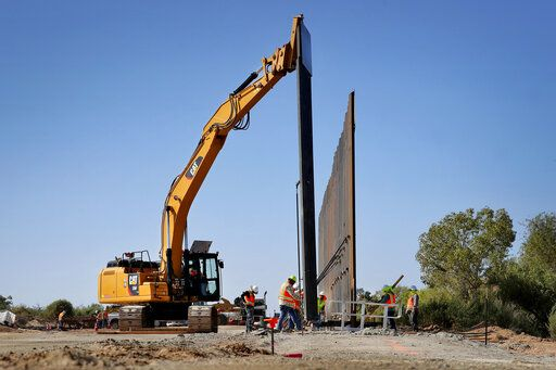 Government contractors erect a section of Pentagon-funded border wall along the Colorado River, Tuesday, Sept. 10, 2019 in Yuma, Ariz. The 30-foot high wall replaces a five-mile section of Normandy barrier and post-n-beam fencing, shown at left, along the the International border that separates Mexico and the United States. Construction began as federal officials revealed a list of Defense Department projects to be cut to pay for President Donald Trump's wall.