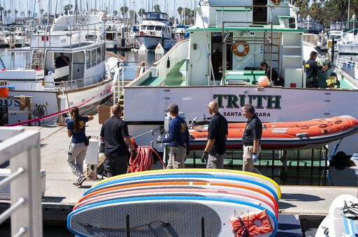 Authorities walk outside the Truth, a Truth Aquatics-owned dive boat, docked in the Santa Barbara Harbor in Santa Barbara, Calif., Sunday, Sept. 8, 2019. Authorities served search warrants Sunday at the Southern California company that owned the scuba diving boat that caught fire and killed 34 people last week.