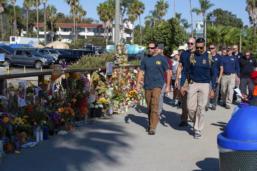 "FBI agents walk past a memorial for the victims of the Conception dive boat on the Santa Barbara Harbor, as authorities issue a search warrant for the Truth Aquatics' offices in Santa Barbara, Calif., Sunday, Sept. 8, 2019. The office was ringed in red ""crime scene"" tape as more than a dozen agents took photos and carried out boxes. Thirty-four people died when the Conception burned and sank before dawn on Sept. 2. They were sleeping in a cramped bunkroom below the main deck and their escape routes were blocked by fire."