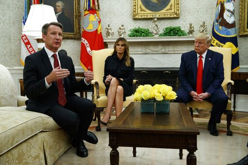 President Donald Trump and first lady Melania Trump listen as acting FDA Commissioner Ned Sharpless talks about a plan to ban most flavored e-cigarettes, in the Oval Office of the White House, Wednesday, Sept. 11, 2019, in Washington.