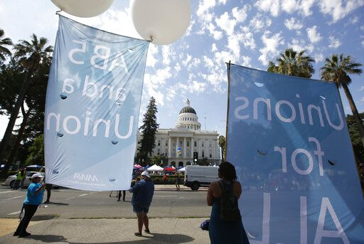 Supporters of a measure to limit when companies can label workers as independent contractors display banners in support of the bill during a rally at the Capitol in Sacramento, Calif., Wednesday, Aug. 28, 2019. If approved by the legislature and signed by Gov. Gavin Newsom, AB5, by Assemblywoman Lorena Gonzalez, D-San Diego, would require companies like Uber and Lyft to treat their drivers like employees.