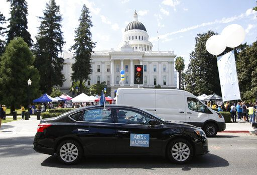 Dozens of supporters of a measure to limit when companies can label workers as independent contractors circle the Capitol during a rally in Sacramento, Calif., Wednesday, Aug. 28, 2019. If approved by the legislature and signed by Gov. Gavin Newsom, AB5, by Assemblywoman Lorena Gonzalez, D-San Diego, would require companies like Uber and Lyft to treat their drivers like employees.