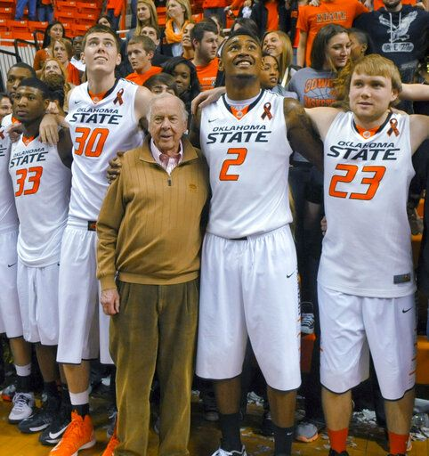 FILE - In this March 2, 2013, file photo, oil tycoon and Oklahoma State supporter T. Boone Pickens, center, celebrates with Oklahoma State's basketball team members Marcus Smart (33), Mason Cox (30), Le'Bryan Nash (2) and Alex Budke, right, following the team's win over Texas in an NCAA college basketball game in Stillwater, Okla. Pickens, a brash and quotable oil tycoon who grew even wealthier through corporate takeover attempts, died Wednesday, Sept. 11, 2019. He was 91.
