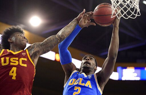 FILE - In this Feb. 28, 2019, file photo, UCLA forward Cody Riley, right, grabs a rebound away from Southern California guard Kevin Porter Jr. during the first half of an NCAA college basketball game in Los Angeles. The NCAA's Board of Governors is urging Gov. Gavin Newsom not to sign a California bill that would allow college athletes to receive money for their names, likenesses or images. In a six-paragraph letter to Newsom, the board said the bill would give California schools an unfair recruiting advantage. As a result, the letter says, the NCAA would declare those schools ineligible for its events.