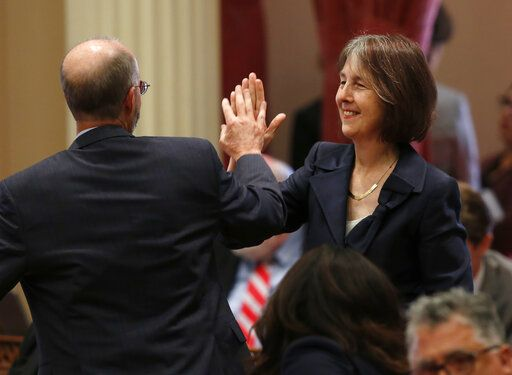 Sen. Nancy Skinner, D-Berkeley, and Sen. Steven Glazer, D-Orinda slap palms in celebration after her measure to let athletes at California colleges hire agents and sign endorsement deals was approved by the Senate in Sacramento, Calif., Wednesday, Sept. 11, 2019. The bill now goes to Gov. Gavin Newsom, who has not said whether he will sign it.