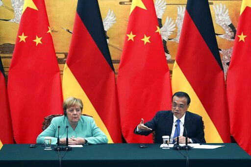Chinese Premier Li Keqiang gives a speech during the press conference at the end of the meeting with Chancellor of Germany Angela Merkel, left, at The Great Hall Of The People in Beijing, on Friday, Sept. 6, 2019. (Andrea Verdelli/Pool Photo via AP)