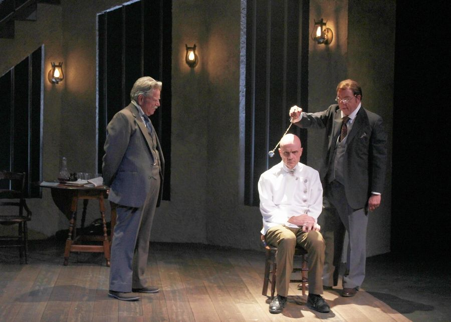 "Dr. John Watson (Norm Woodel), left, and Dr. Evans (Matt Penn), right, try to elicit the truth from a psychiatric inmate (Mike Speller) claiming to be the late Sherlock Holmes in Buffalo Theatre Ensemble's ""Holmes and Watson."""