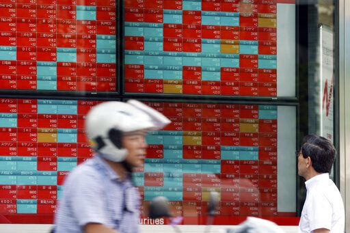 A man looks at an electronic stock board showing Japan's Nikkei 225 index at a securities firm in Tokyo Thursday, Sept. 12, 2019. Asian shares were mixed Thursday after China moved to ease trade tensions.