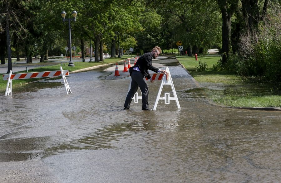 A Lincolnshire Marriott Resort employee fixes a barricade to block flooded road leading into the resort in Lincolnshire. No one was allowed in and shuttles were used to evacuate guests from the hotel on Friday.