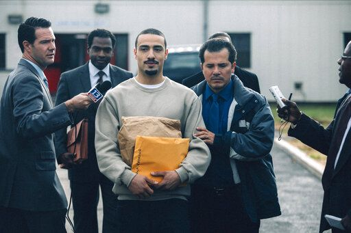 "This image released by Netflix shows Freddy Miyares as Adult Raymond Santana Jr. and John Leguizamo as Raymond Santana Sr., right, in a scene from ""When They See Us."" Leguizamo returns to the Emmy Awards as a nominee for his performance in the Netflix docudrama. He is currently in Los Angeles at the Ahmanson Theatre for a six-week run of his Tony-nominated one-man show ""Latin History for Morons,� in which he offers an eye-opening lesson about the participation of Latin Americans throughout U.S. history.  (Atsushi Nishijima/Netflix via AP)"