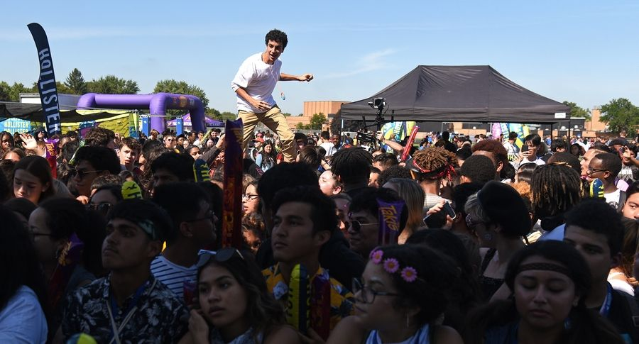A student stands on someone's shoulders for a better view of Almost Monday onstage at Larkin High School in Elgin during a free musical festival Monday.