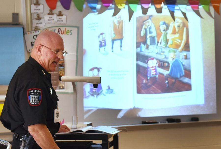 "Wauconda Police Chief David Wermes reads ""Small Saul"" to fourth-graders Monday at Wauconda Grade School."