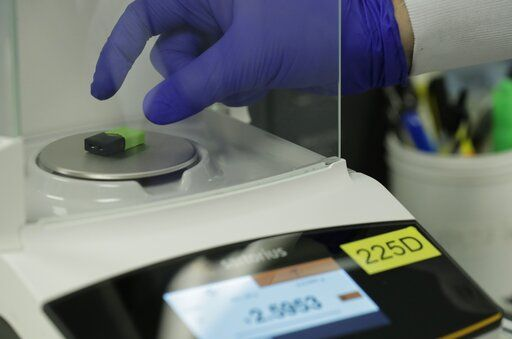 A Green Machine brand CBD vape pod is weighed during testing at Flora Research Laboratories in Grants Pass, Ore., on July 18, 2019. As part of an investigation into CBD vapes, The Associated Press commissioned the lab to test vape products purchased around the country, including seven Green Machine pods bought at stores in California, Florida and Maryland. Four of the Green Machine pods contained synthetic marijuana, a dangerous street drug commonly known as K2 or spice.