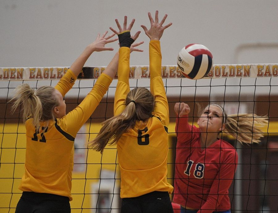 Dundee-Crown's MacKenzie Field sends a shot past Jacobs' Maggie Wallenberger and Kylie Bruns in a girls volleyball match in Algonquin Tuesday.