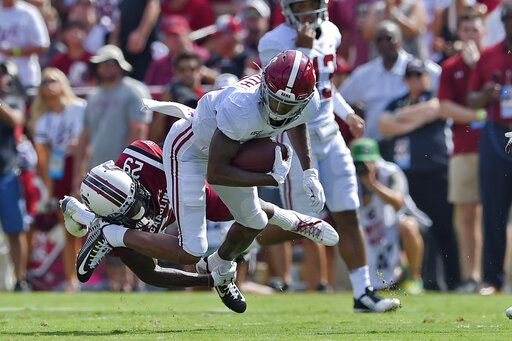 Alabama's DeVonta Smith, top, rushes while defended by South Carolina's J.T. Ibe during the first half of an NCAA college football game Saturday, Sept. 14, 2019, in Columbia, S.C.