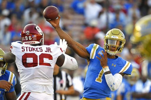 UCLA quarterback Dorian Thompson-Robinson, right, passes while under pressure from Oklahoma defensive lineman LaRon Stokes during the first half of an NCAA college football game Saturday, Sept. 14, 2019, in Pasadena, Calif.
