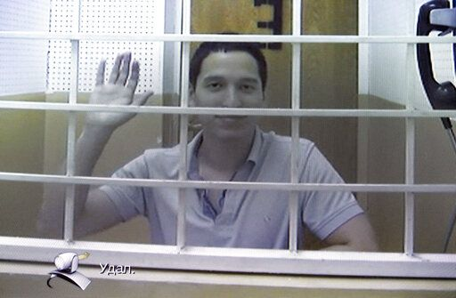 FILE - In this Wednesday, Aug. 21, 2019 file photo, Aidar Gubaidulin waves at the camera as he takes part in a court hearing via a video link in Moscow, Russia. Russian prosecutors on Wednesday Sept. 18, 2019, are asking to release protester Aidar Gubaidulin, facing years in prison for assaulting police following a mounting public campaign in support of anti-government activists and even bystanders caught up in an opposition rally.
