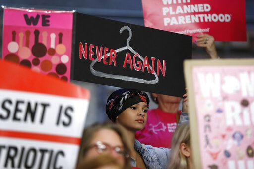 FILE - In this May 21, 2019 file photo, August Mulvihill, of Norwalk, Iowa, center, holds a sign during a rally to protest recent abortion bans at the Statehouse in Des Moines, Iowa. A new report released Wednesday, Sept. 18, shows that the number and rate of abortions across the U.S. have plunged to their lowest levels since the procedure became legal nationwide in 1973.
