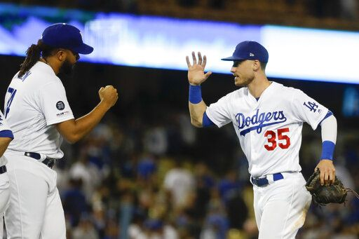 Los Angeles Dodgers right fielder Cody Bellinger, right, celebrates after their 7-5 win against the Tampa Bay Rays with relief pitcher Kenley Jansen after a baseball game in Los Angeles, Tuesday, Sept. 17, 2019.