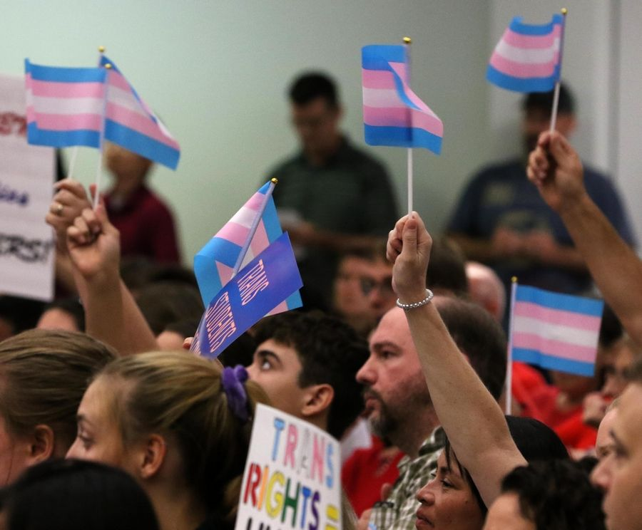 Supporters of transgender students' using the locker rooms of their choice, without a previous requirement that they change in privacy stalls, rally at the school board meeting at Palatine High School.
