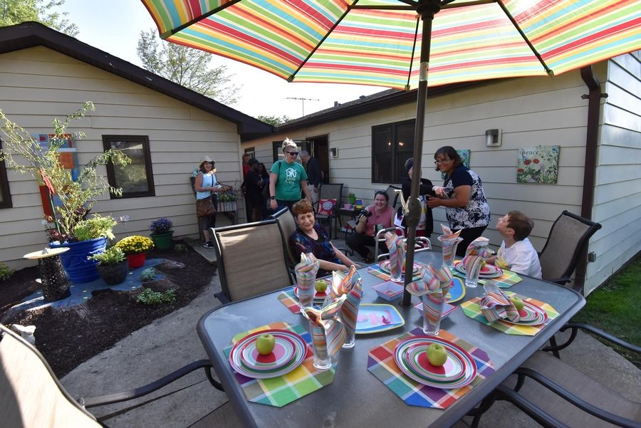 Residents of a Palatine group home operated by Little City gather with some of the volunteers who gave the property a makeover Wednesday once the work was complete.