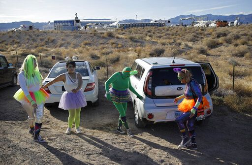 "From left, Alex Clark, Carolyn Milner, Audrie Clark and Lucinda Clark dance near their car outside of the Storm Area 51 Basecamp event Friday, Sept. 20, 2019, in Hiko, Nev. The event was inspired by the ""Storm Area 51"" internet hoax."