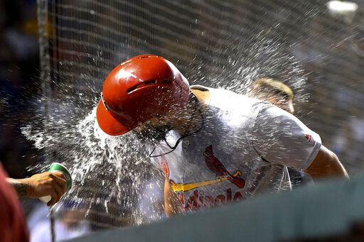 St. Louis Cardinals' Matt Carpenter is doused with water in the dugout after he hit a home run against the Chicago Cubs during the 10th inning of a baseball game Thursday, Sept. 19, 2019, in Chicago.